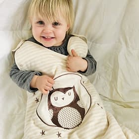Toddler wearing beige sleeping bag with owl embroided on the front
