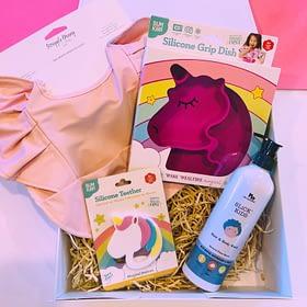 Girls first birthday gift box with pink bib and unicorn plate