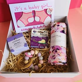 Gift box with Baby items. Nail trimmer, baby balm,swaddle in a roll with flowers on it