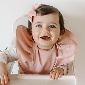 Baby wearing a pin frilly bib